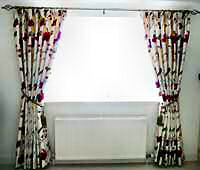 Embroidered silk interlined curtains on a metal pole.